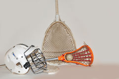 Lacrosse stick and goalie equipment. Womens Lacrosse stick with ball, goalie helmet and goalie stick on a white background Stock Image