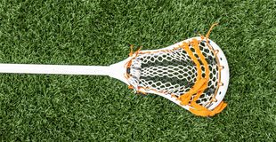 Lacrosse stick on green turf. A white lacrosse stick with some orange trim on green turf royalty free stock photography