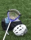 Lacrosse stick, helmet and bag. A purple goalie lacrosse stick is resting on an athletes gear bag with a helmet next to both on the ground royalty free stock photography