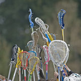 Lacrosse sticks reaching to the sky. High school girls Lacrosse team raise thier sticks to the sky at the start of a game stock image