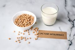 Lactose free milk concept. Homemade milk of nuts and piece of paper with text LACTOSE INTOLERANCE on marble background, non dairy. Milk from organic substitute royalty free stock photos