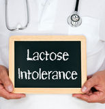 Lactose Intolerance. Doctor or physician holding chalkboard with text Stock Photos