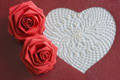 heart and paper roses. A white lacy heart and two paper flowers Stock Images