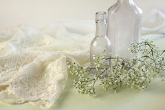 Lacy Negligee with Vintage Apothecary Bottles. Lacy negligee with two vintage apothecary bottles and baby breath flowers stock photo