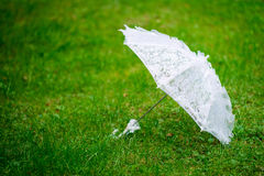Lacy parasol. Lacy white parasol on the green grass stock image