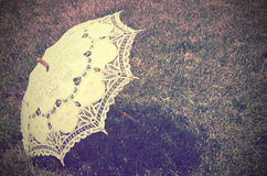 Lacy parasol on the grass. tinted vintage Royalty Free Stock Photos
