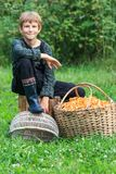 Lad sitting near basket full of chanterelles Royalty Free Stock Image