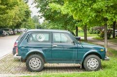 Lada Niva verde 4x4 fora do carro da estrada estacionou na rua Fotos de Stock Royalty Free