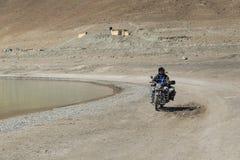 Ladakh, la India - julio 10,2014: Montar a caballo del motorista en el lago Pangong fotos de archivo libres de regalías