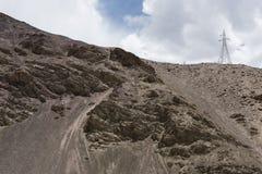 Ladakh mountain landscape and a transmission tower. Transmission tower in rocky barren mountain terrain of Ladakh, India, Asia royalty free stock image