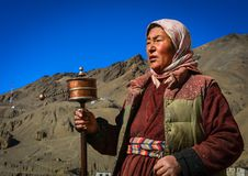 A LADAKHI WOMAN SPINNING PRAYER WHEEL AT LAMAYURU MONASTERY stock images