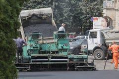 Ladda asfalt i en asfaltspreader Arkivfoto