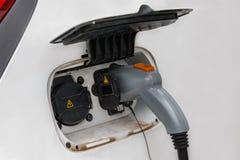 Ladda en elbil med tillförselen för maktkabel pluggade från special station royaltyfria bilder