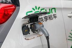 Ladda en elbil med tillförselen för maktkabel pluggade från special station på gatan i den turist- staden Yangshuo av Kina royaltyfri bild