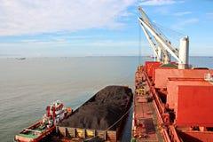 Ladda kol från lastpråm på en bärare som i stora partier använder skeppkranar och hastiga grepp på porten av Samarinda, Indonesie arkivfoton