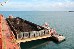 Ladda kol från lastpråm på en bärare som i stora partier använder skeppkranar och hastiga grepp på porten av Samarinda, Indonesie arkivfoto