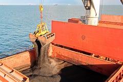 Ladda kol från lastpråm på en bärare som i stora partier använder skeppkranar och hastiga grepp på porten av Samarinda, Indonesie royaltyfri bild