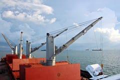 Ladda kol från lastpråm på en bärare som i stora partier använder skeppkranar och hastiga grepp på porten av Samarinda, Indonesie royaltyfria foton