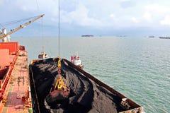 Ladda kol från lastpråm på en bärare som i stora partier använder skeppkranar och hastiga grepp på porten av Samarinda, Indonesie arkivbild