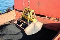 Ladda kol från lastpråm på en bärare som i stora partier använder skeppkranar och hastiga grepp på porten av Samarinda, Indonesie arkivbilder