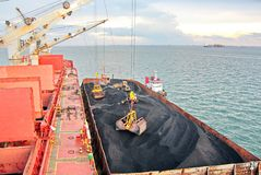 Ladda kol från lastpråm på en bärare som i stora partier använder skeppkranar och hastiga grepp på porten av Samarinda, Indonesie royaltyfri fotografi