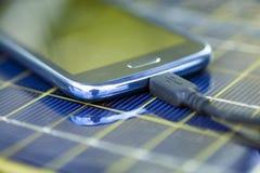 Laddande mobiltelefon med den sol- uppladdaren Arkivbilder