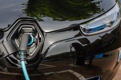 Laddande modern elbil med strömförsörjning som in pluggas Royaltyfria Foton