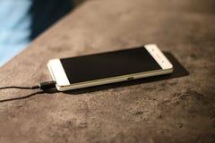 Laddande smart telefon för vit på grafitskrivbordet Royaltyfri Fotografi