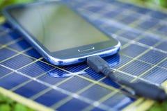 Laddande Smart-telefon med den sol- uppladdaren Fotografering för Bildbyråer