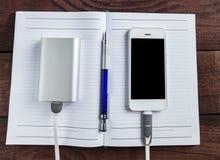 Laddande Smartphone med den Grey Portable External Battery And pennan royaltyfri foto