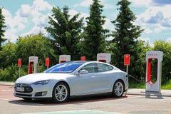 Laddande Tesla modell S Battery på den Tesla kompressorstationen Royaltyfri Fotografi