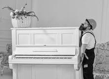 Laddaren flyttar pianoinstrumentet Kuriren levererar möblemang i fall att av flyttar sig ut, förflyttning Hemsändningbegrepp man arkivbild
