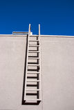 Ladder. A ladder on a white wall with blue sky bakcground Royalty Free Stock Photo