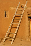 Ladder. Leaning on a adobe building Stock Image