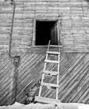 Ladder die tegen een schuurzolder leunen stock foto