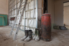 Ladder, dusty and dirty rubber boots of workers and big gas boiler in apartment during during on the remodeling Stock Photos