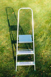 Ladder on green lawn background Royalty Free Stock Photography