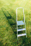 Ladder on green lawn background Royalty Free Stock Image