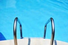Ladder in het blauwe zwembad stock foto's