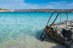 Ladder leading down into a beautiful blue sea Royalty Free Stock Photo