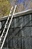 Ladder leans on a metal shed Royalty Free Stock Photos