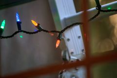 Glass panes showing christmas lights and a ladder. Ladder leans up against home and window with christmas lights decoating the outdoors royalty free stock image