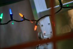 Ladder and christmas lights outside of a home window. Ladder leans up against home and window with christmas lights decoating the outdoors stock photo