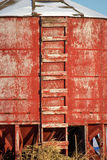 A ladder nailed to round grain bin. A red painted ladder nailed to a wood grain bin Stock Photo