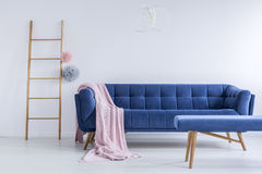 Ladder and navy blue sofa. Colorful pompoms on ladder next to navy blue sofa with pink blanket in living room with stool stock photography