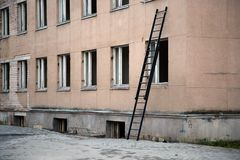 Ladder near building with broken windows Stock Image
