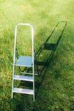 Ladder op groene gazonachtergrond stock afbeelding