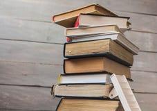 Ladder op stapel van oude boeken op houten achtergrond stock afbeeldingen