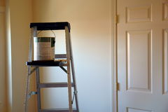 Ladder with paint can and brush. In freshly painted room, lit by sun and showing a door Royalty Free Stock Image