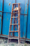 Ladder. Paint-splattered old wood ladder leaning against a bright blue metal dumpster Royalty Free Stock Images